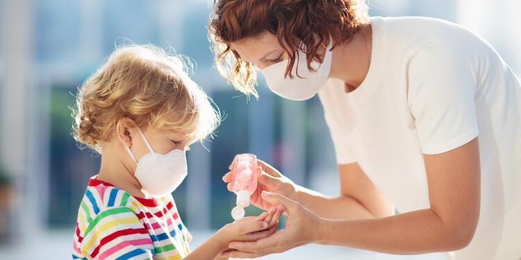 Mother helping child hand sanitize to stay safe from coronavirus